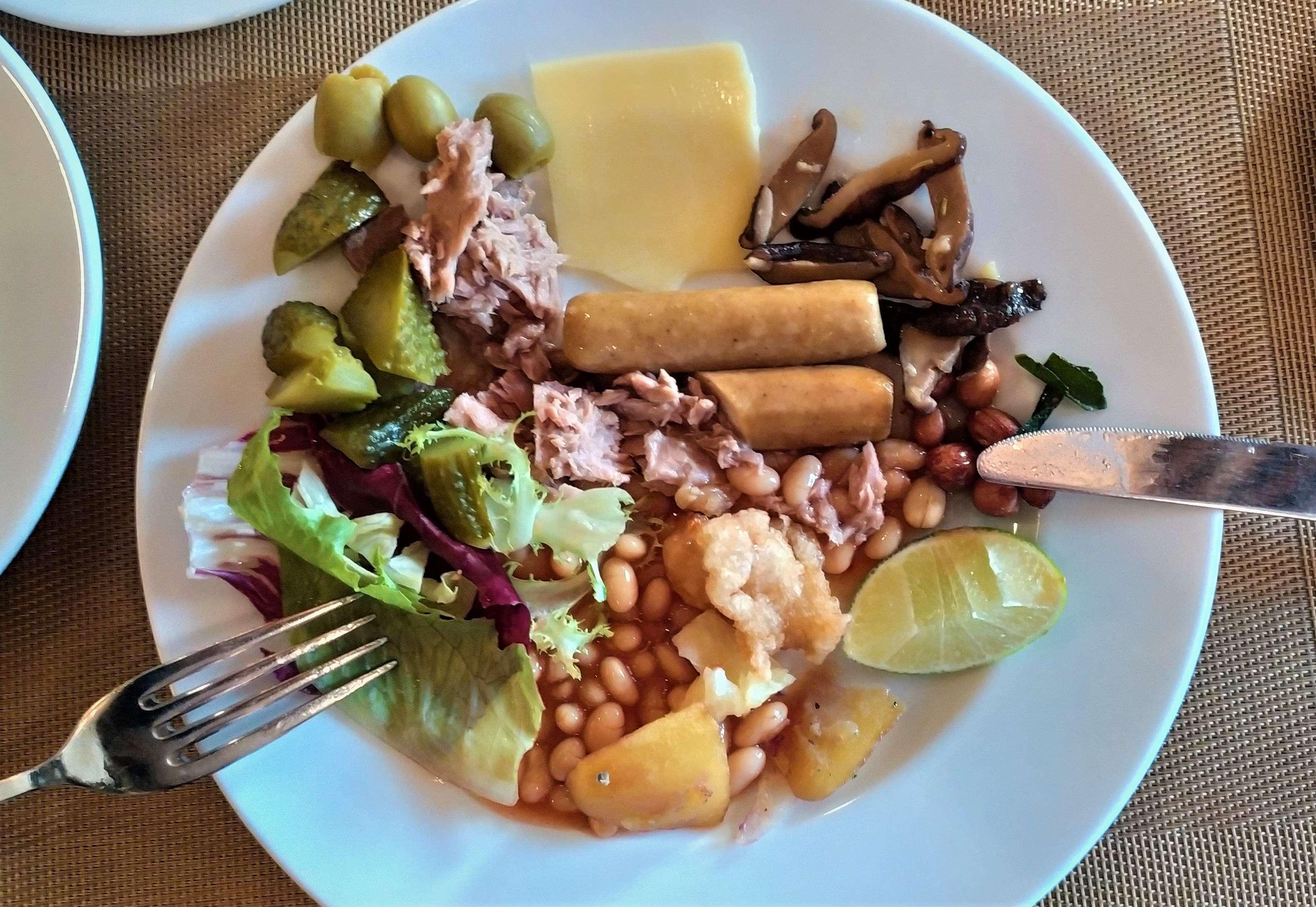Завтрак с мясом морского тунца, куриными сосисками, белой фасолью, сыром, оливками, грибами, корнишонами, арахисом, кусочком рыбы в кляре, листьями салата и долькой лайма. Очень скромно и скоромно…